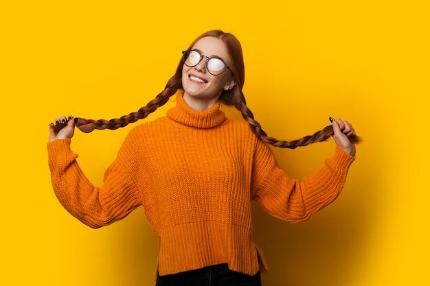 Милая молодая кавказская девушка с рыжими волосами, держащая ее за хвост, одетая в оранжевый свитер, позирует на желтом фоне