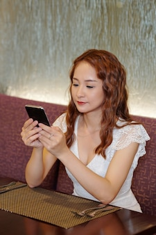 Прекрасная молодая очаровательная женщина сидит за столиком в кафе, ждет заказа и отвечает на текстовые сообщения