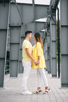 Lovely young couple in bright clothes holding hands