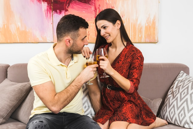 Lovely young couple holding wineglasses looking at each other