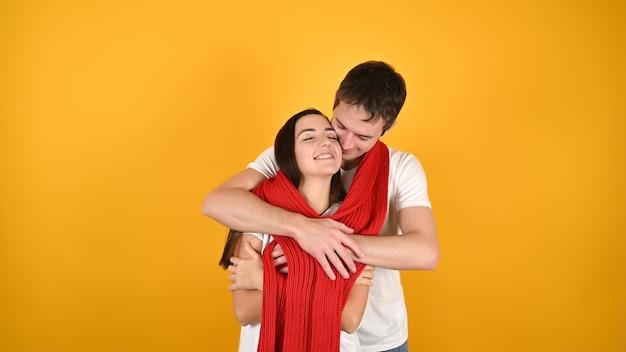 Прекрасная молодая пара обниматься. портрет счастливой молодой пары с красным теплым шарфом перед желтым фоном. празднование дня святого валентина.