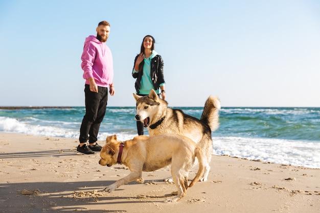 Прекрасная молодая пара играет со своей собакой на пляже