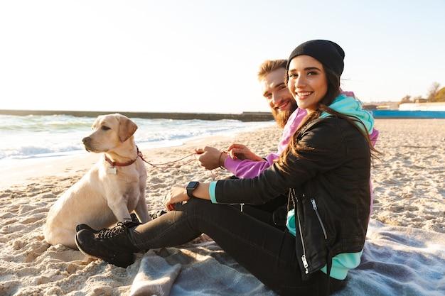 해변에서 자신의 강아지와 함께 연주 사랑스러운 젊은 부부