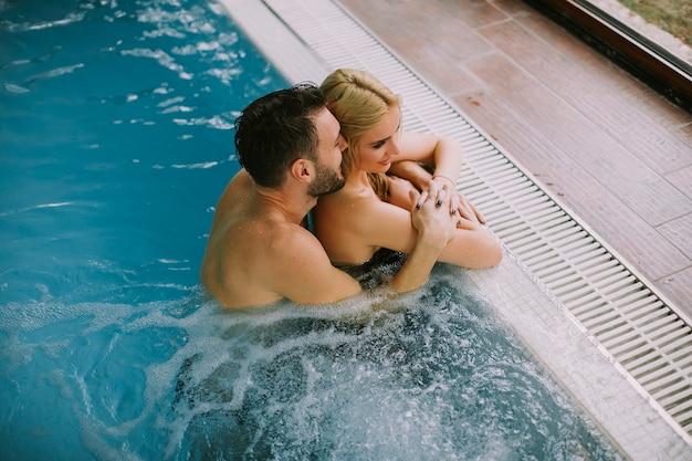Прекрасная молодая пара отдыхает у бассейна во внутреннем бассейне