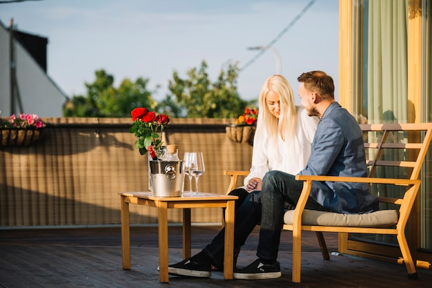 ワインの氷のバケツと眼鏡で屋上に座っている素敵な若いカップル
