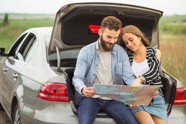 Lovely young couple sitting in the car trunk searching destinations in the map