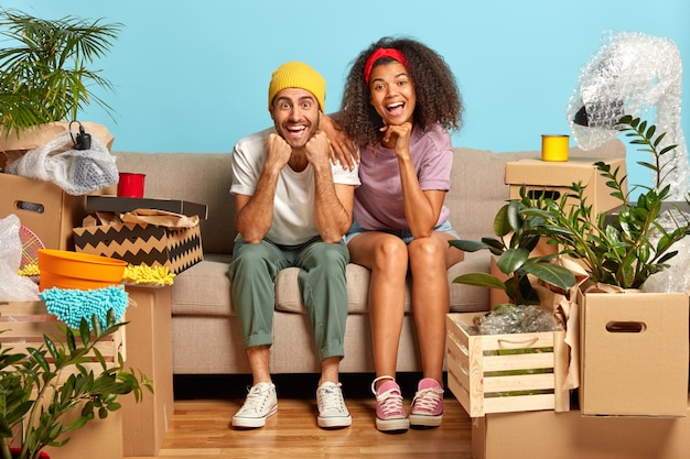상자에 둘러싸인 소파에 앉아 사랑스러운 젊은 부부