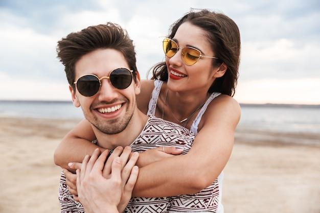 Прекрасная молодая пара весело проводит время на пляже, обнимаясь