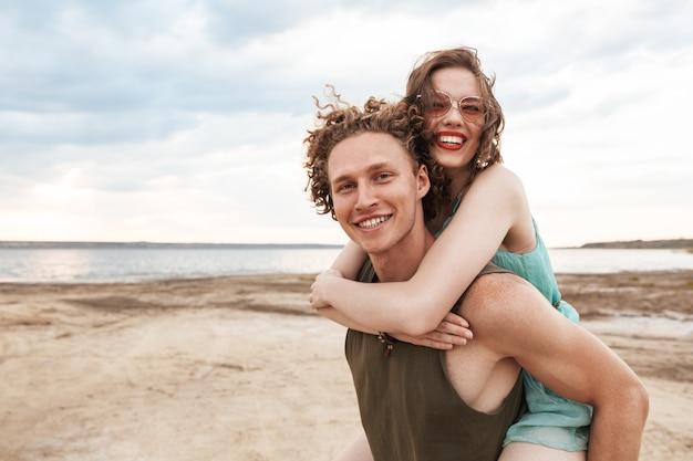 Прекрасная молодая пара весело проводит время на пляже, катаясь на спине