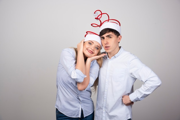 Bella giovane coppia in piedi in cappelli di babbo natale sul muro grigio.