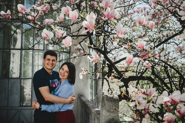 Lovely young couple stands under blooming tree outside and hug each other tender