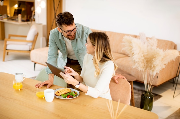 Lovely young couple using digital tablet and having breakfast in the kitchen
