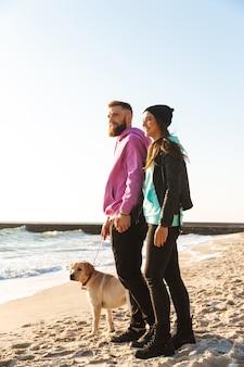 Прекрасная молодая пара гуляет со своей собакой на пляже