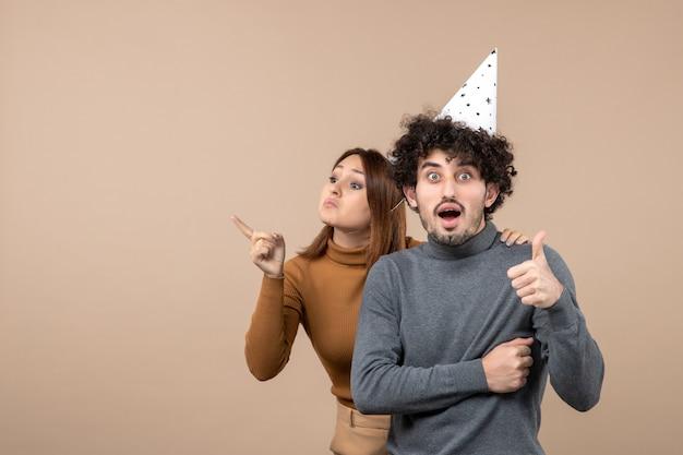 Милая молодая пара в новогодней шапке злая девушка смотрит на что-то, стоящее за парнем на сером
