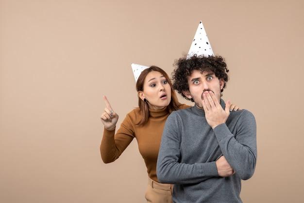 사랑스러운 젊은 부부는 회색에 충격을받은 남자 뒤에 서 찾고 새해 모자 화가 소녀를 착용