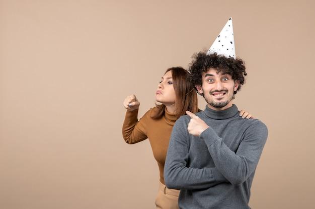 사랑스러운 젊은 부부는 회색에 남자 뒤에 서있는 새해 모자 화가 소녀를 착용