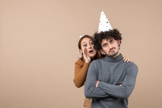 素敵な若いカップルは、心配している男の後ろに立って灰色でおしゃべりする新年の帽子の女の子を着ています