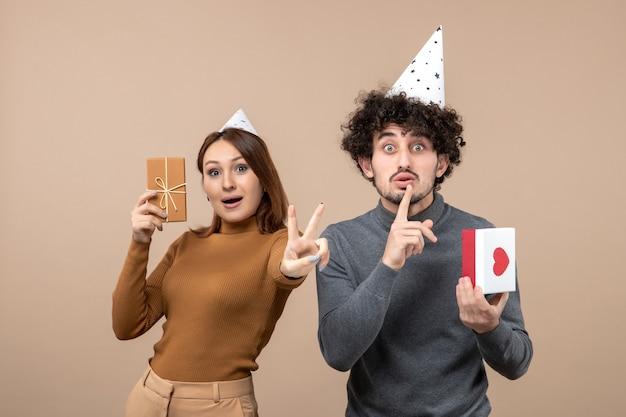 La giovane coppia adorabile indossa la ragazza del cappello del nuovo anno con il regalo che fa il ragazzo teso di gesto di vittoria con il cuore che fa il gesto di silenzio su gray
