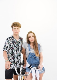 Lovely young couple with bicycle on white background