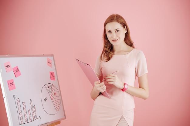 チャート、図、ステッカーでホワイトボードに立っている財務部門の素敵な若い女性マネージャー