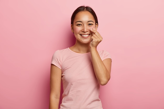 Lovely young female model touches genlty her rouge cheeks, shows healthy skin on face, has asian appearance, smiles broadly, wears pink t shirt, poses indoor. people, ethnicity, beauty, skin care