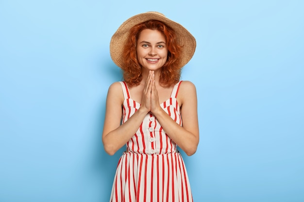 Lovely young female models indoor, keeps palms pressed together, being thankful for help, wears summer striped dress, straw hat,  isolated on blue wall. people, body language