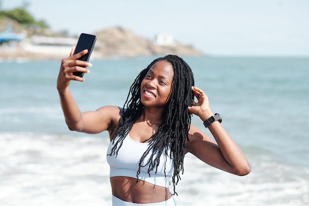 海岸に立って、トレーニングを終えた後に自分撮りをしている素敵な若いフィットの女性