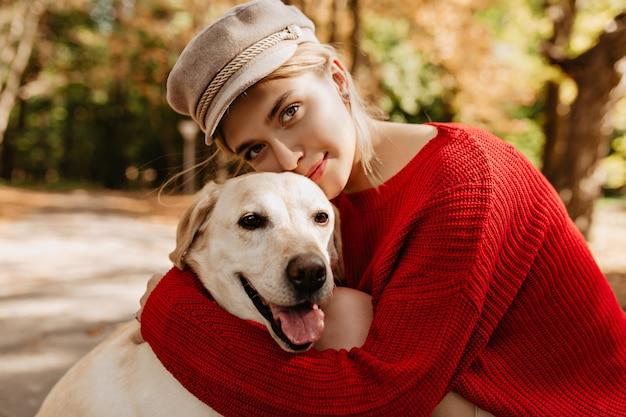 숲에서 래브라도 포옹 좋은 유행 빨간 스웨터에 사랑스러운 어린 소녀. 공원에 앉아 그녀의 강아지와 함께 가벼운 모자에 예쁜 금발.