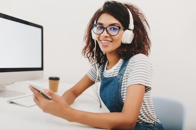 Милая молодая девушка в полосатой рубашке сидит в офисе и держит смартфон в руке, ожидая звонка