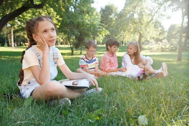 Милая молодая девушка, мечтательно глядя в сторону, отдыхает после учебы со своими одноклассниками
