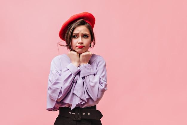 Милая молодая девушка делает невинное лицо. портрет дамы в берете и стильной блузке на розовом фоне.