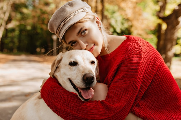 Lovely young girl in nice trendy red pullover hugging labrador in the forest. pretty blonde in light hat with her dog sitting in the park.