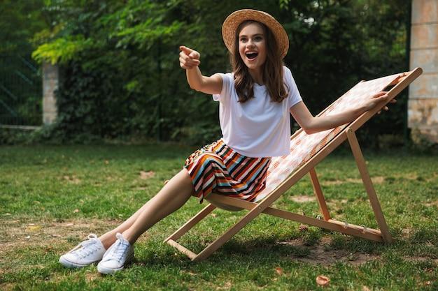 Прекрасная молодая девушка отдыхает на гамаке в городском парке на открытом воздухе летом, указывая пальцем