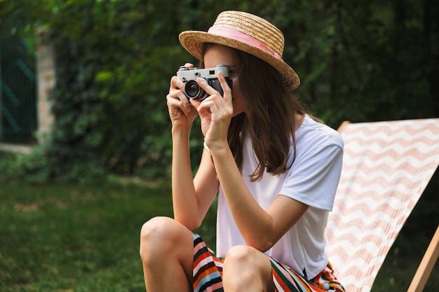 여름에 야외 도시 공원에서 해먹에 쉬고 사랑스러운 어린 소녀, 사진 카메라로 사진을 찍고