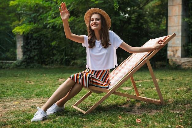 Прекрасная молодая девушка отдыхает на гамаке в городском парке на открытом воздухе летом, машет рукой