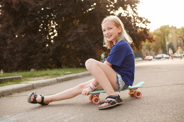 Lovely young girl sitting on her penny board, smiling