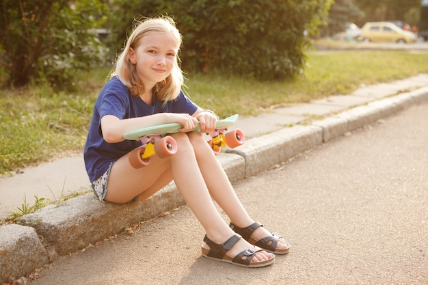 Lovely young girl smiling joyfully, resting after skating on her pennyboard, copy space
