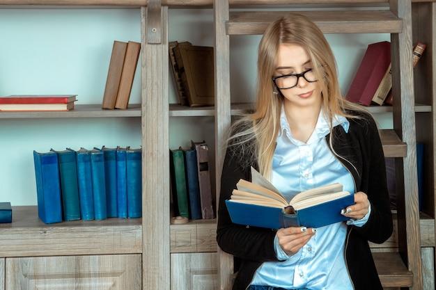 本棚の近くで本を読んで眼鏡をかけた素敵な若い女の子の学生