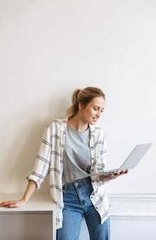Прекрасная молодая девушка студент учится с портативным компьютером в кафе в помещении