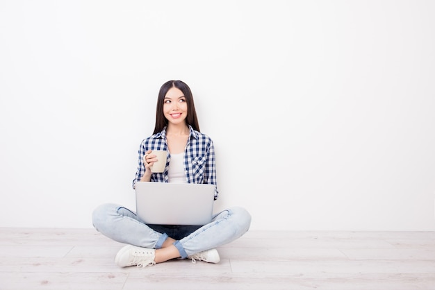 Милая молодая девушка в повседневной одежде сидит на полу и пьет кофе на пк