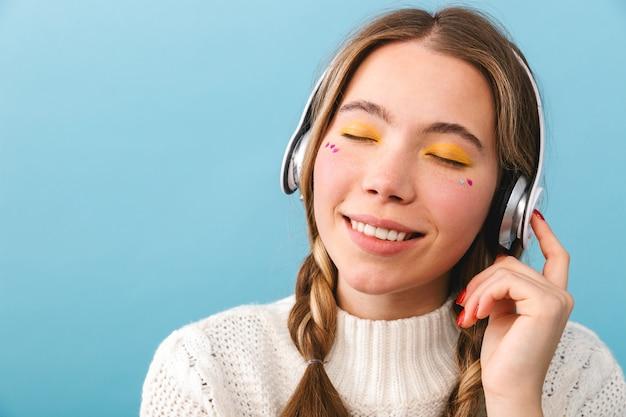 헤드폰으로 음악을 듣고 격리 된 서 겨울 옷을 입고 사랑스러운 어린 소녀