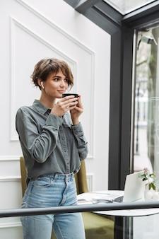 Милая молодая девушка в беспроводных наушниках пьет кофе, стоя в кафе в помещении