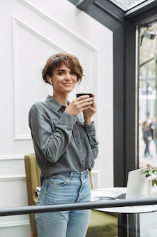 Lovely young girl wearing wireless earphones drinking coffee while standing at the cafe indoors