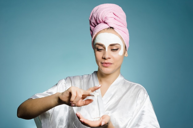 彼女の頭にピンクのタオルを持つ素敵な若い女の子は彼女の顔に白い栄養価の高いマスクを置きます
