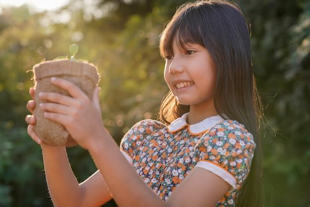 새싹과 밝은 황금빛 아침 햇살을 가진 사랑스러운 어린 소녀.