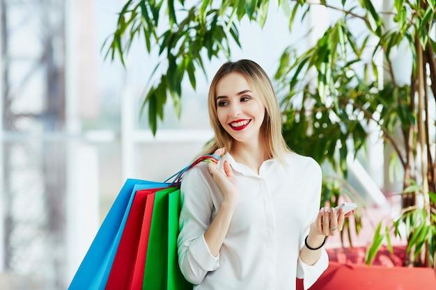 白いブラウスを着て、カラフルな買い物袋を持って立っている、携帯電話、ショッピングコンセプト、コピースペースを持っている薄茶色の髪と赤い唇を持つ素敵な若い女の子。