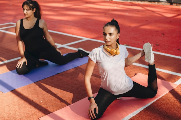 Lovely young girlfriends doing stretching exercises before losing weight exercises in the morning in a sport park.