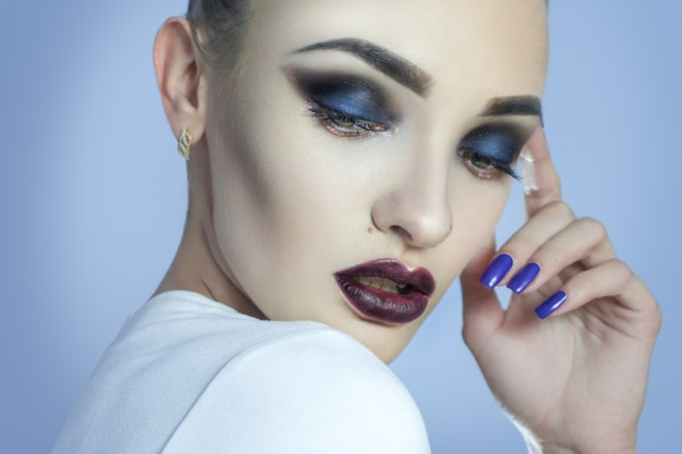 Lovely young lady with beautiful make up looking away in studio