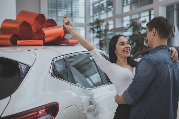 Lovely young married couple buying new car together