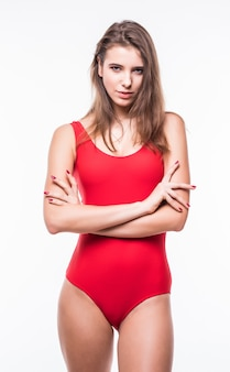 Lovely young model girl in red swimming suite holds arms on her belt isolated on white background